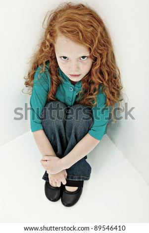 Worried sad young girl child sitting alone in corner.