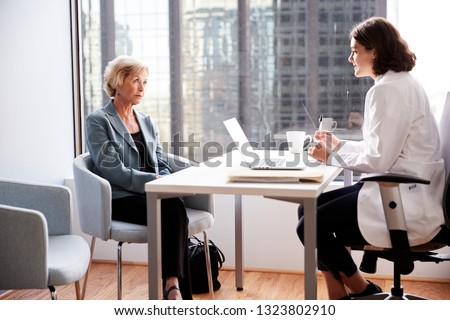 Worried Senior Woman Having Consultation With Female Doctor In Hospital Office
