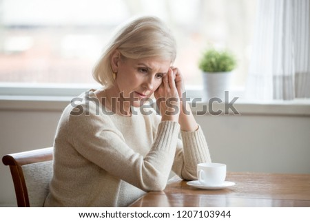 Worried senior woman sitting at table at home lost in thoughts, concerned aged female distracted from reality thinking about problems, sad elderly wife grieve missing husband or remembering past