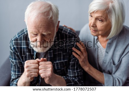 worried senior woman touching husband suffering from dementia and sitting with clenched fists Foto stock ©