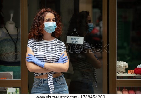 Worried shop assistant on her retail business door during the pandemic quarantine covid 19 in Spain.