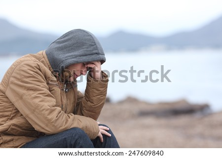 Worried teenager guy crying on the beach in winter in a bad weather day
