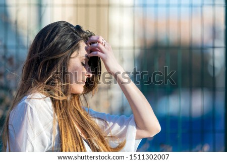 Worried teenager woman outdoors in a sunny day.