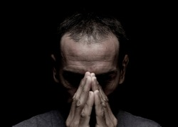 worried white mid aged man crestfallen praying in deep black background  in front position with unsaturated colors
