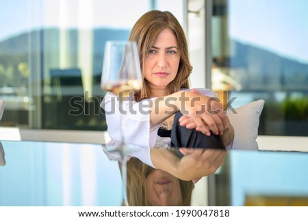 Worried withdrawn woman sitting staring at a glass of wine thinking deeply with a sombre expression outdoors at a table on her patio with reflection on the table Photo stock ©