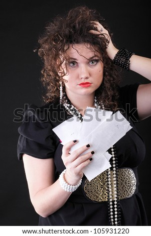 Worried woman calculating her bills shopping over black background
