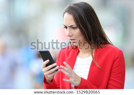 Worried woman in red reading bad news on smart phone standing in the street
