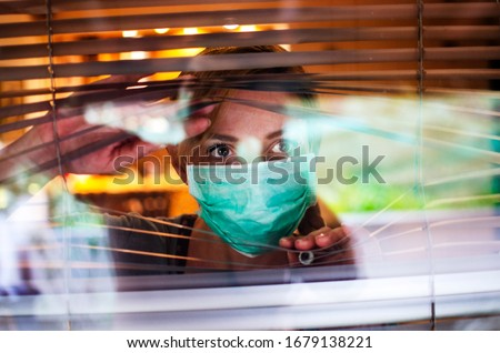 Worried Woman looking through window from home in quarantine during Coronavirus.Anxiety Woman in self distancing isolation due to Covid-19.Stay at home in time of pandemic concept