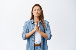 Worried woman need something, begging for help and say please. Girl apologizing, making clingy sad face and pleading you, standing against white background