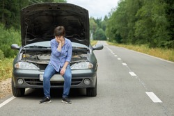 Worried woman sits on the bumper of her old broken car on the narrow rural road in summer