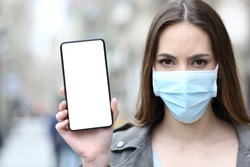 Worried woman wearing protective mask showing smart phone blank screen in the street