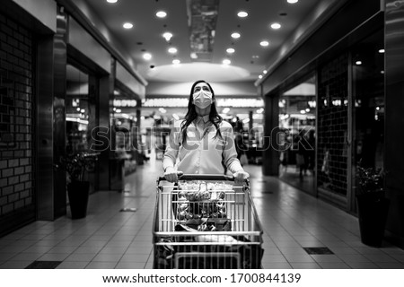 Worried woman with mask groceries shopping in supermarket,pushing trolley.Food panic buying and hoarding.Covid-19 quarantine shopper.Financial problems anxiety.Unemployed person in money crisis