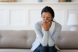 Worried young african american woman sitting on sofa, thinking of personal problems alone indoors, copy space. Unhappy mixed race lady feeling frustrated or nervous, suffering from loneliness.