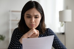 Worried young asian woman sit at desk read official bank notification about debt penalty fee warning of financial problem. Concerned vietnamese business lady dissatisfied by bad news from paper letter