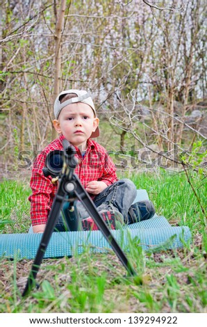 Worried young boy sitting on a mat on the ground in the countryside beside a tripod mounted rifle with a scope attached as he waits for his Dad