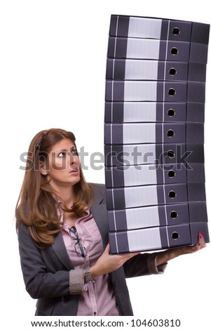 Worried young businesswoman holding a big pile of document ring binders, symbolizing work overload concept and exploitation by assigning too much work - stock photo
