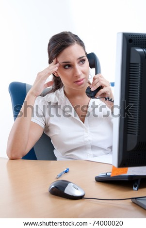 Worried young businesswoman receiveing bad news over the phone