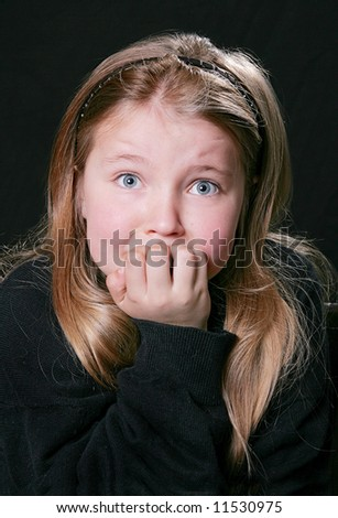 worried young child over a black background