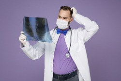 Worried young doctor man in medical gown face mask safe from coronavirus hold X-ray of lungs fluorography roentgen put hand on head isolated on violet background. Healthcare personnel health concept