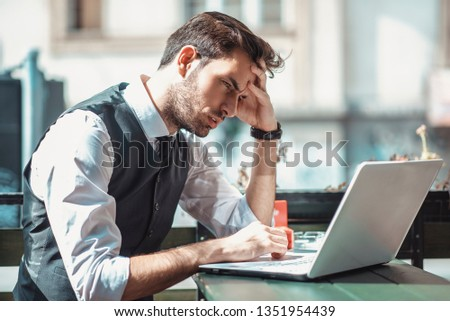 Worried young entrepreneur receiving worrying and bad news over his cell phone