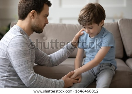 Worried young father holding hand of stressed little kid son, giving psychological help at home. Compassionate kind daddy supporting depressed offended small boy suffering from school bullying. Stock photo ©