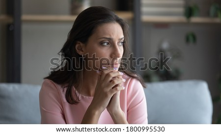 Worried young indian Arabic woman sit on couch at home look in distance thinking pondering, anxious unhappy arab mixed race female suffer from mental psychological personal problems, mourn or yearn