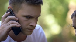 Worried young man calling 911 to report crime or ask for medical help, closeup
