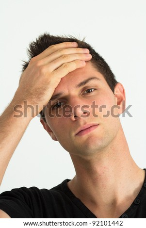 Worried young man with hand at face