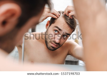 Worried young shirtless man examining his hair while looking at the bathroom mirror