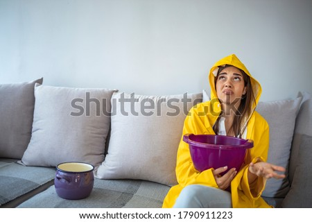 Worried young woman in raincoat holding bucket under water drops. Upset young woman using bucket during leak in living room. Frustrated brunette woman sitting on sofa under leaking ceiling