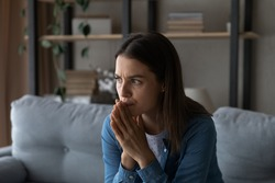 Worried young woman sit on sofa look aside lean forward with folded hands feel fear anxiety. Teen female stressed with unwanted pregnancy thinking on abortion hesitate have doubts making hard decision