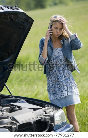 Worried young woman with her broken car, calling for assistance
