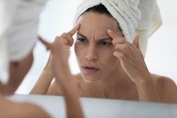 Worried young woman wrapped in towel looking in mirror in bathroom, finding skin defects, touching forehead, discovering pimples, acne, wrinkles. Facial skin problems, cosmetology concept
