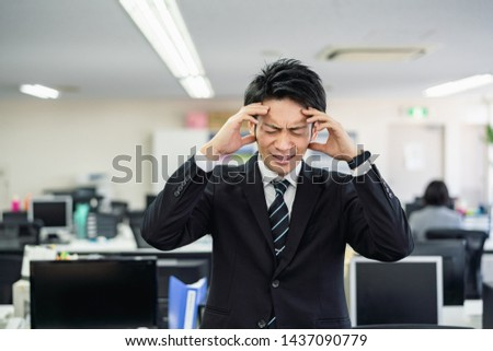 worrying asian businessman in office.