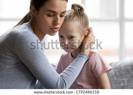 Worrying young mother comforting little stressed crying daughter, head shot. Loving mommy apologizing to offended small kid girl, stroking her head, showing care indoors, family conflict concept. Stock photo ©