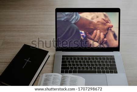Worship from home, Online live church for sunday service, Laptop screen with close up prayer hands, Bible on wooden table, quarantine for Covid 19 situation