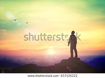 Worshipping concept: Silhouette of humble man standing to talking with God in mountain autumn sunset background - Shutterstock ID 651526222