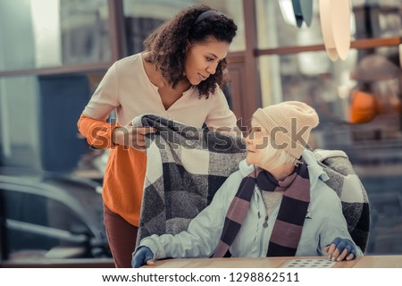 Would you like anything. Pleasant kind woman talking to her guest while taking care of her