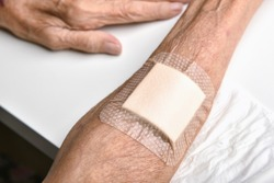 Wound bandage, Dressing arm wound with sterile plaster pad, Accidental wound care treatment in elder old man.