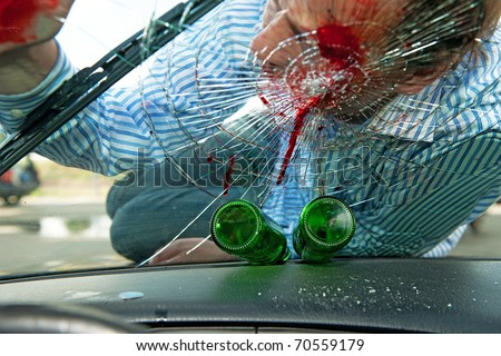 Wounded pedestrian with his head on the smashed windscreen of a car, with two empty beer bottles on the dashboard - the effects of drinking and driving