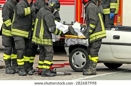 wounded person carried by firefighters on a stretcher after the road accident