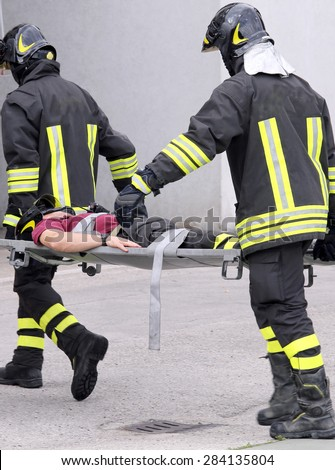 wounded person carried by two firefighters on a stretcher during training in the firehouse