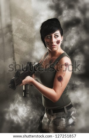 wounded special tactics sexy woman holding up her weapon in a battlefield