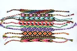 Woven DIY friendship bracelets handmade of embroidery bright thread with knots isolated on white background.