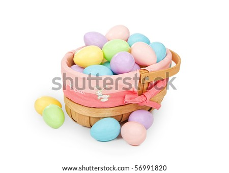 Woven Easter basket with pastel color plastic eggs. Isolated on white.