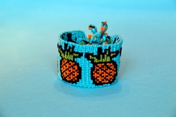 Woven friendship bracelet with alpha pattern pineapples handmade of thread on blue background