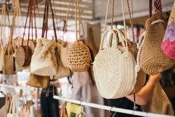 Woven handbags hanging in outdoor store
