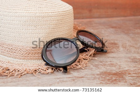 Woven hat is placed on a wooden table, and with sunglasses.