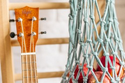 woven macrame food bag with apples hanging on the stairs next to ukulele, Zero-waste, ecology, recyclable product
