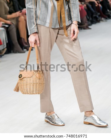 Woven women's brown rattan bag is in woman's hand. Fashion model stands on the catwalk  #748016971